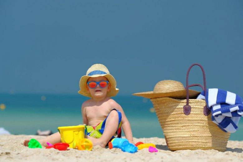 Wypoczywając na skąpanej w słońcu dubajskiej plaży, należy pamiętać o okularach przeciwsłonecznych i odpowiednim nakryciu głowy dla malucha