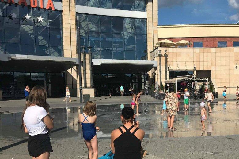 Dzieci kąpiące się w fontannie przed centrum handlowym