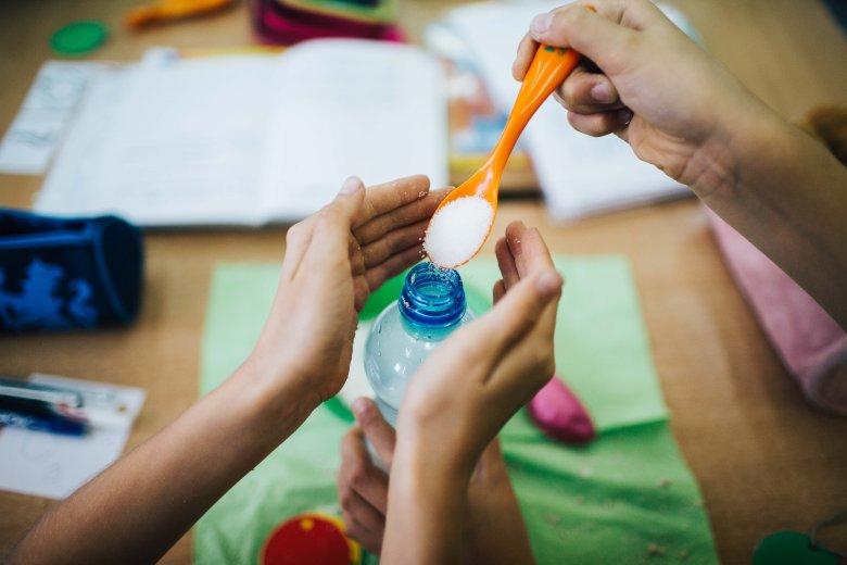 Dzieci w skupieniu realizowały eksperyment z drożdżami, współpracując między sobą w parach.